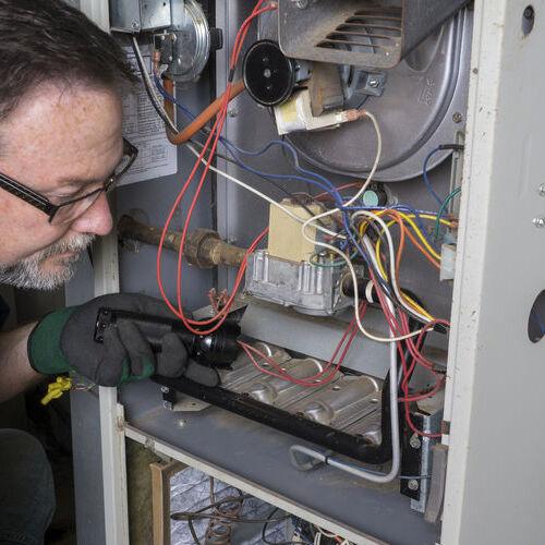 A Technician Checks a Furnace.