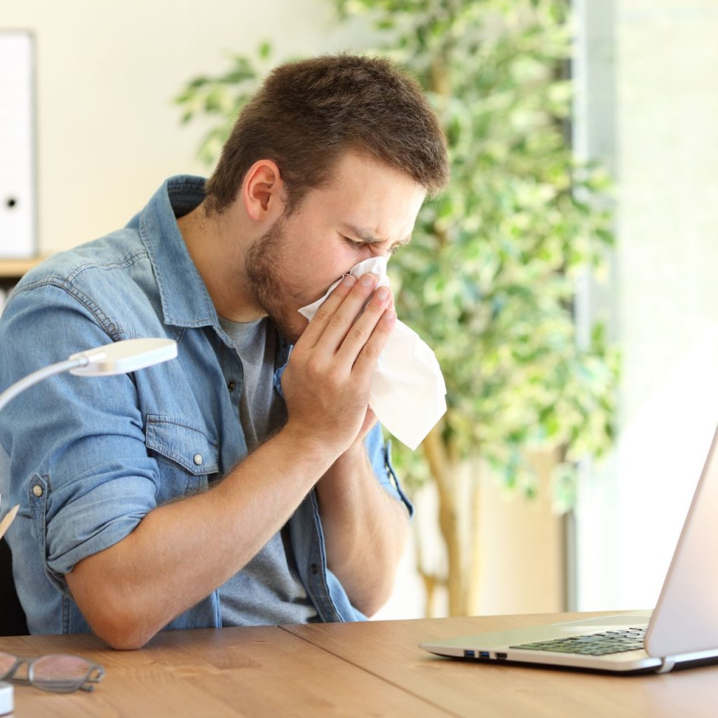 man sneezing because of dry air in the home
