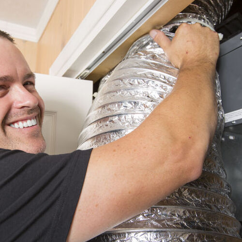 A Technician Working on an Air Duct.
