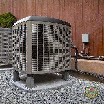 An AC Condenser Sits Outside Above Gravel