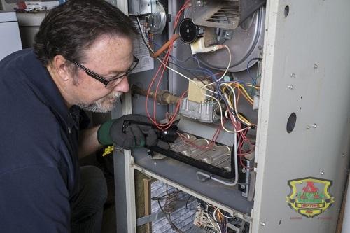 Technician Examining a Gas Furnace's Insides